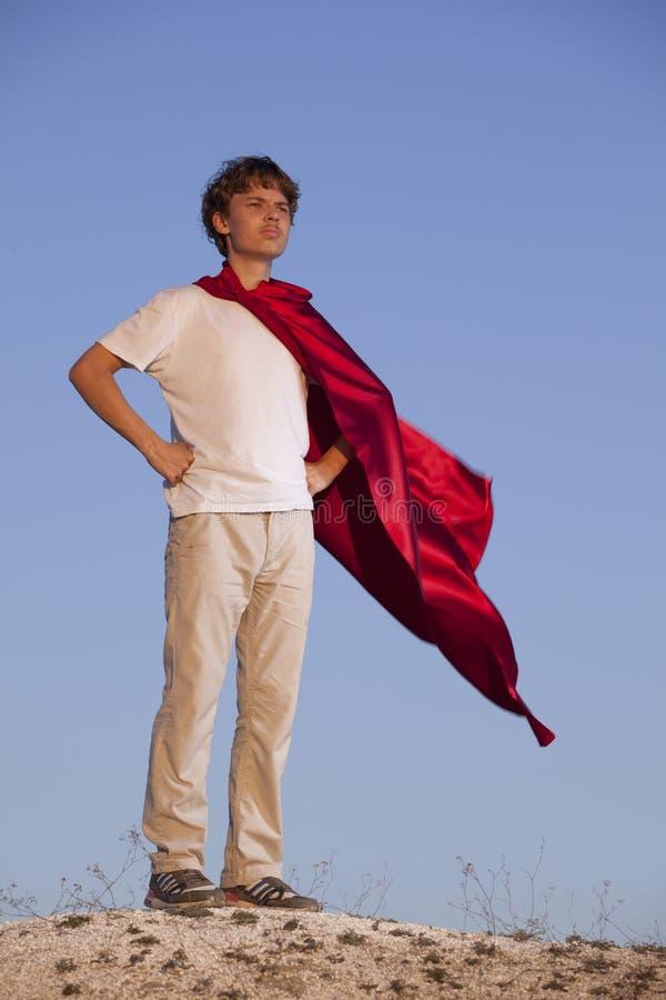Мальчик играя супергероев на предпосылке неба, подростковый супергероя в красном плаще на холме стоковое изображение rf
