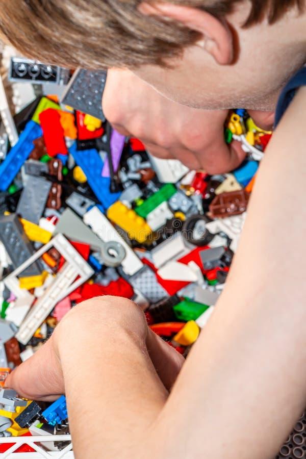 Мальчик играя с пластиковыми игрушками конструкции на поле стоковое изображение rf