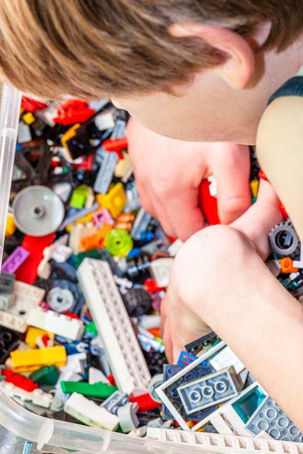 Мальчик играя с пластиковыми игрушками конструкции на поле стоковая фотография
