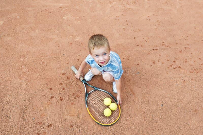 Мальчик играя с ракеткой и шариком тенниса на теннисном корте над взглядом стоковое фото rf