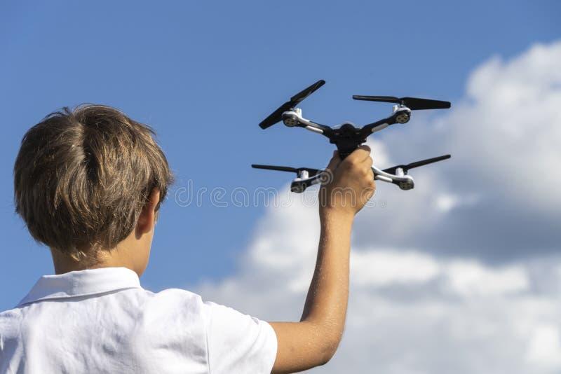 Мальчик играя с трутнем в outdoors летнего дня против голубого неба стоковые фотографии rf