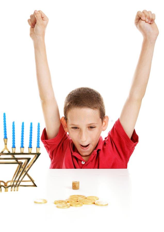 Мальчик играя Dreidel на Hanukkah