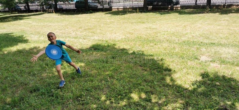 Мальчик играя frisbee стоковое фото