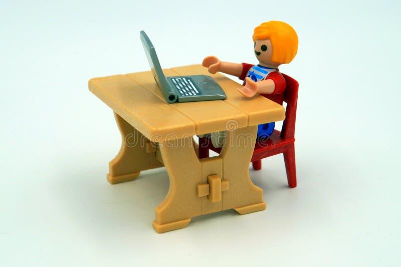 Мальчик игры пристрастившийся сидя за портативным компьютером стоковая фотография rf