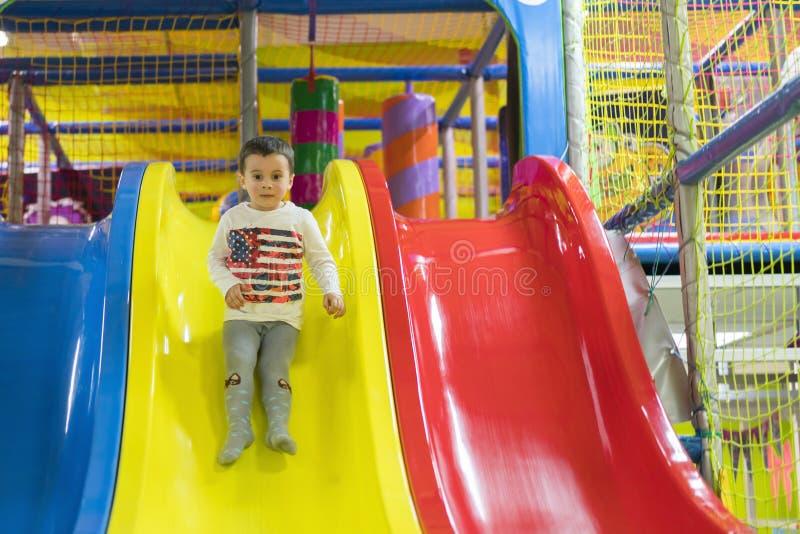 Мальчик идет вниз со скольжения на спортивной площадке Он смеется и имеется потехой на спортзале джунглей Катание мальчика от дет стоковая фотография rf