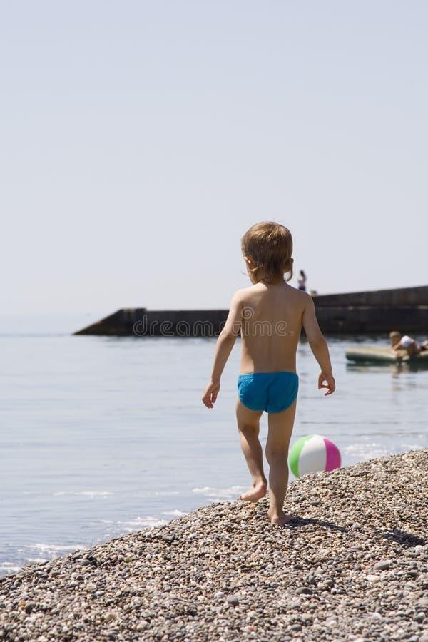 мальчик идет меньший seacoast каменистый стоковое изображение rf