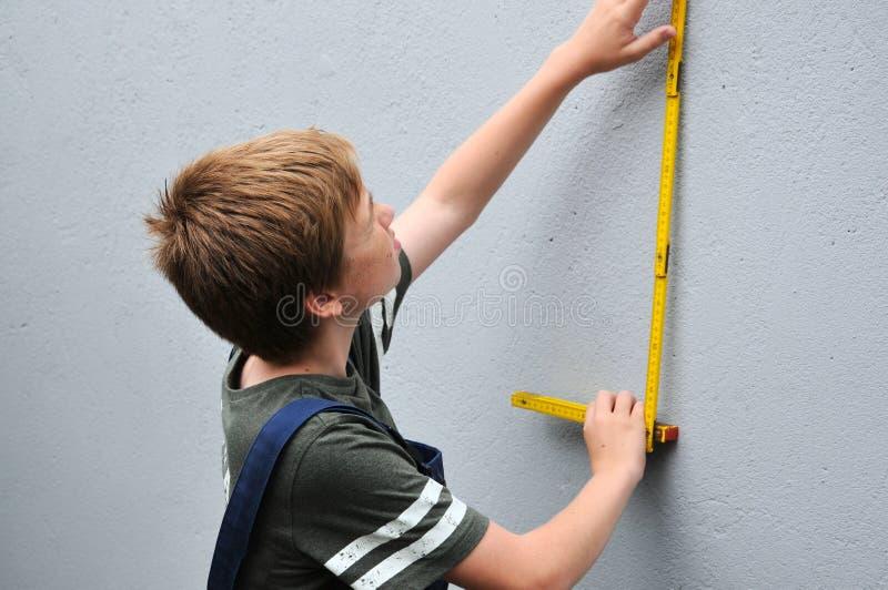 Мальчик измеряет стену с помощью брусу для кантовки листов стоковая фотография rf
