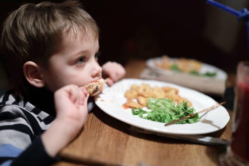 Мальчик имеет kebab на протыкальнике стоковые изображения