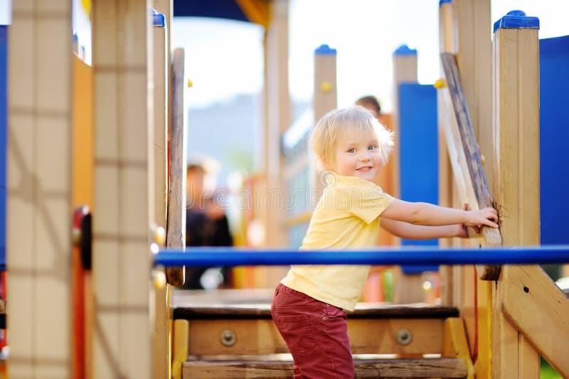 Мальчик имея потеху на внешнем скольжении playground/on стоковые фотографии rf