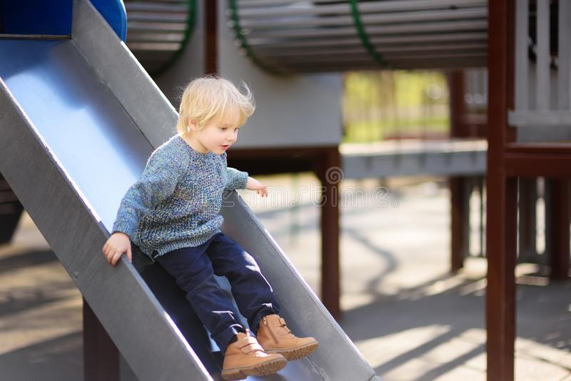 Мальчик имея потеху на внешнем скольжении playground/on стоковое фото rf