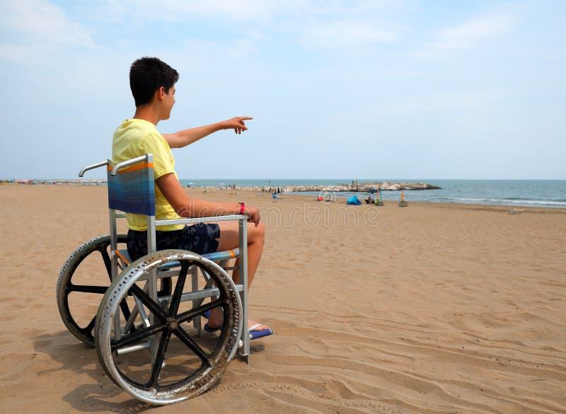 Мальчик-инвалид на инвалидном кресле на пляже указывает на море стоковое фото rf