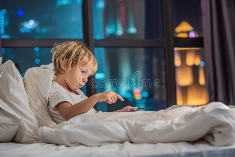 Мальчик использует таблетку в его кровати перед идти спать на ба стоковые фотографии rf