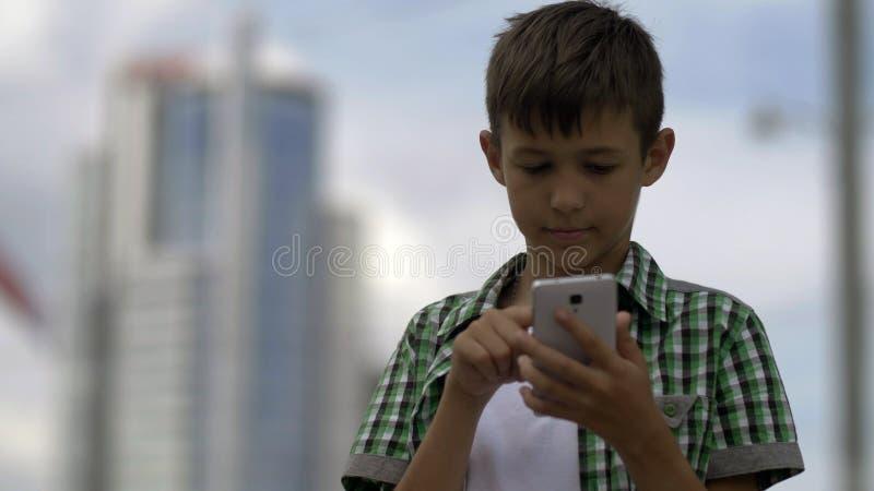 Мальчик использует телефон, шкалы сообщение, и держит в корреспонденции стоковые фотографии rf