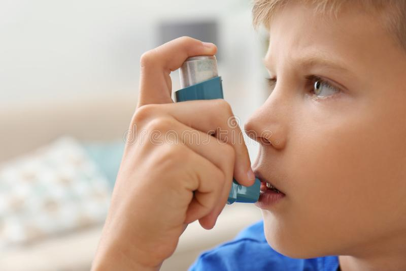 Мальчик используя ингалятор астмы стоковое изображение rf