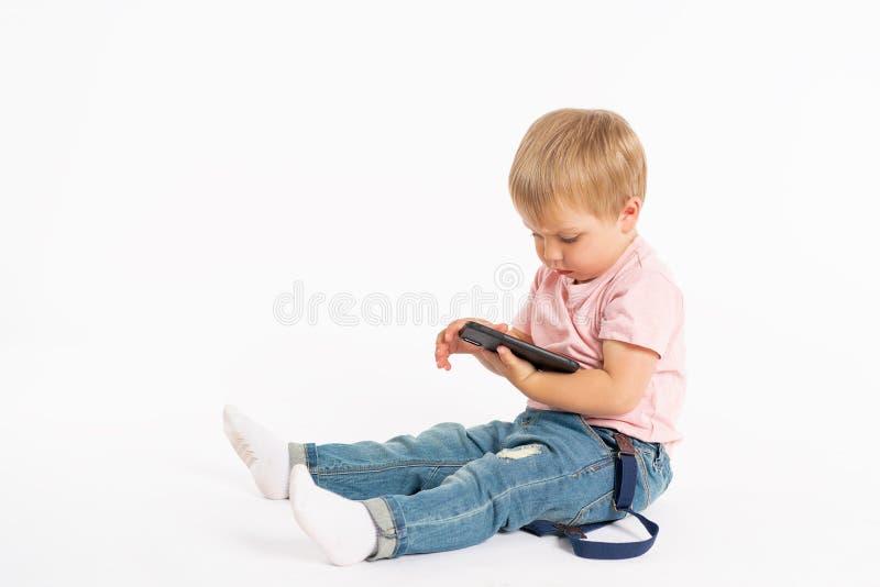 Мальчик используя мобильный телефон Ребенок играя на смартфоне Технология, мобильные приложения, дети и родительское консультатив стоковое изображение rf