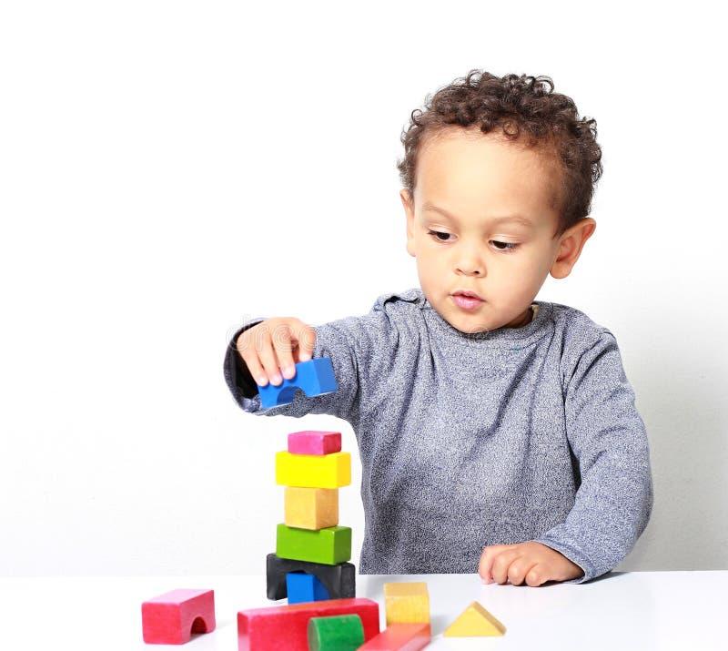 Мальчик испытывая его творческие способности путем построение башен со строительными блоками игрушки стоковые изображения