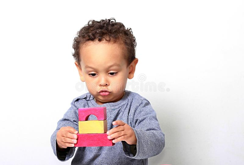 Мальчик испытывая его творческие способности путем построение башен со строительными блоками игрушки стоковые фотографии rf