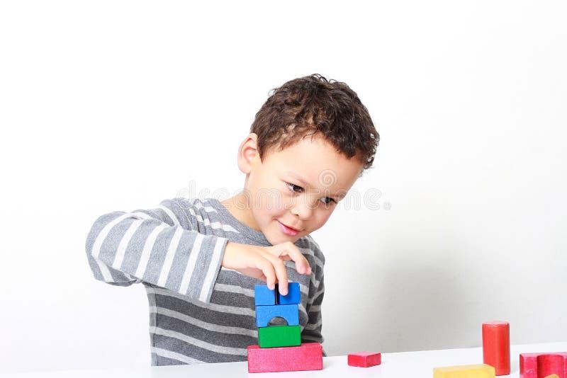 Мальчик испытывая его творческие способности путем построение башен со строительными блоками игрушки стоковое фото rf