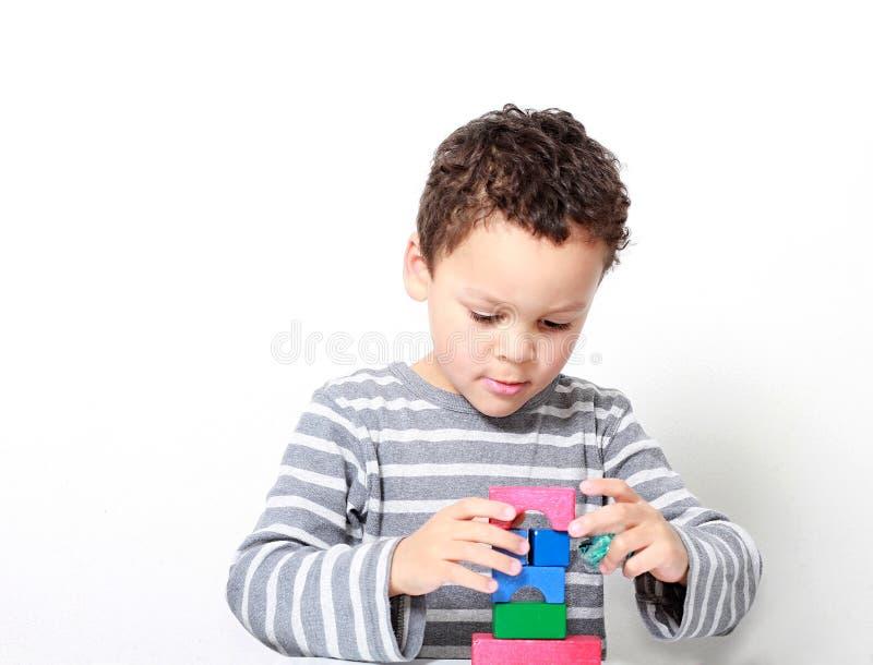 Мальчик испытывая его творческие способности путем построение башен со строительными блоками игрушки стоковые изображения rf