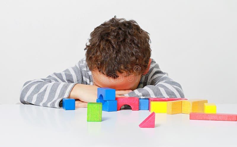Мальчик испытывая его творческие способности путем построение башен со строительными блоками игрушки стоковая фотография rf