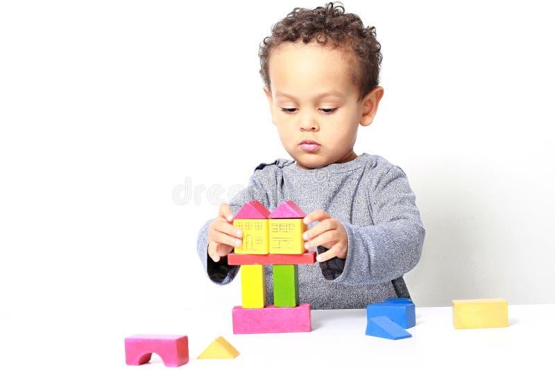 Мальчик испытывая его творческие способности путем построение башен со строительными блоками игрушки стоковые фото