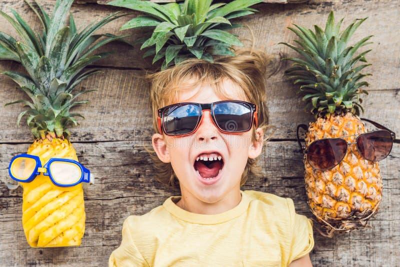 Мальчик и ананасы ананаса на каникулах стоковые фото
