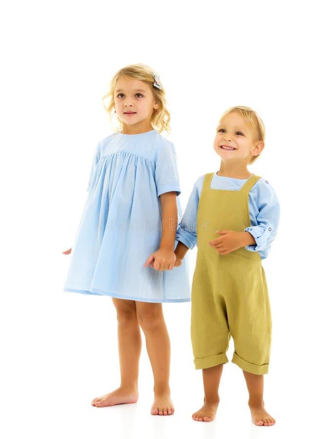 Мальчик и девочка держатся за руки стоковые изображения
