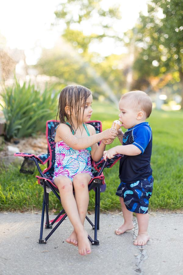 Мальчик и девушка есть мороженое стоковое изображение