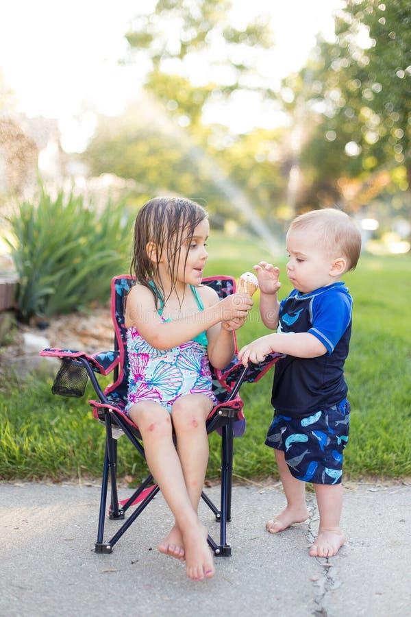 Мальчик и девушка есть мороженое стоковое фото rf