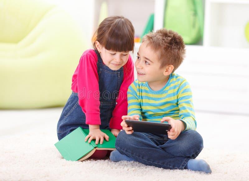 Мальчик и девушка играя или читая от таблетки стоковое изображение rf
