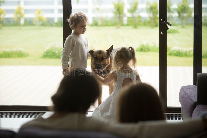 Мальчик и девушка играя с их собакой дома стоковая фотография