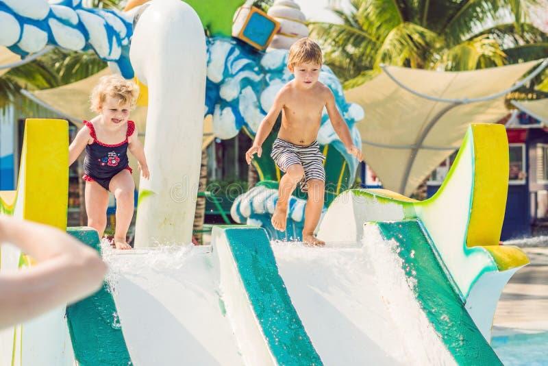 Мальчик и девушка имеют потеху в аквапарк стоковое фото rf