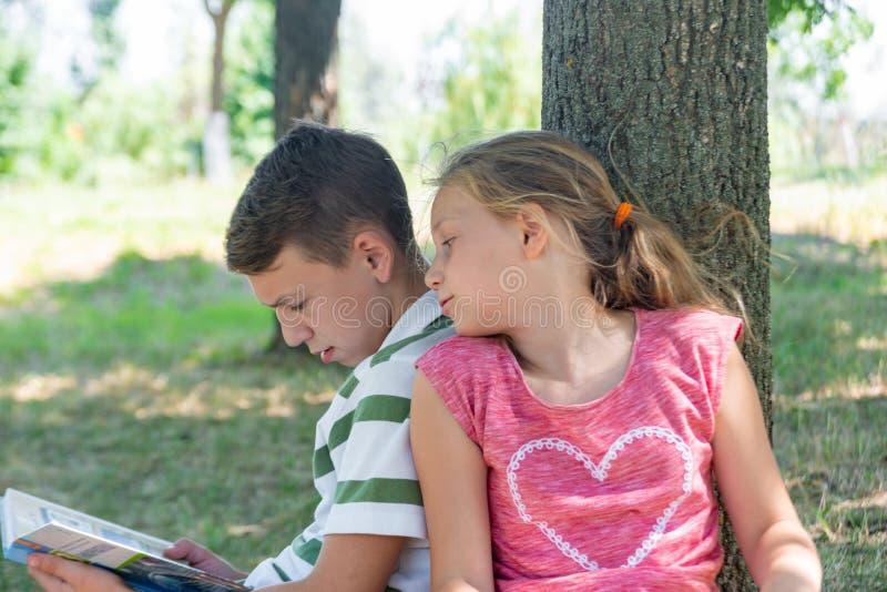 Мальчик и девушка сделать их домашнюю работу в парке и получить готовый для школы совместно стоковые фото