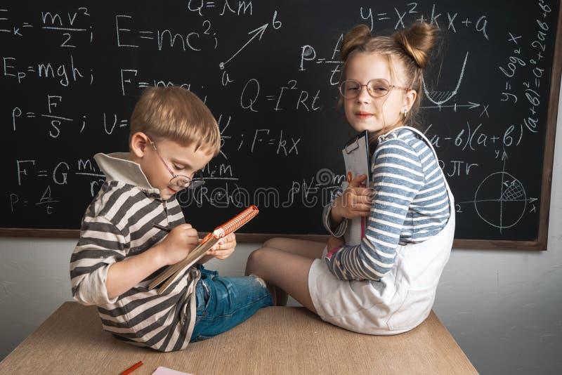 Мальчик и девушка сидят на столе школы и изучают формулы на доске мела стоковое фото rf
