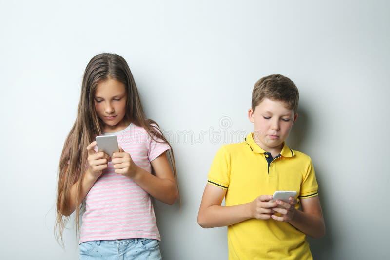 Мальчик и девушка с smartphones стоковое фото