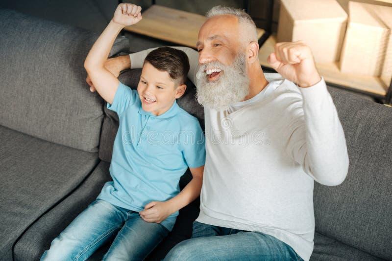 Мальчик и его дед празднуя победу любимой команды стоковые изображения