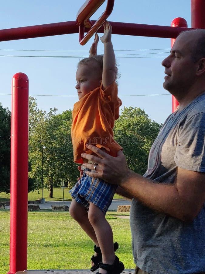 Мальчик и его папа на оборудовании спортивной площадки текстура стоковые изображения rf