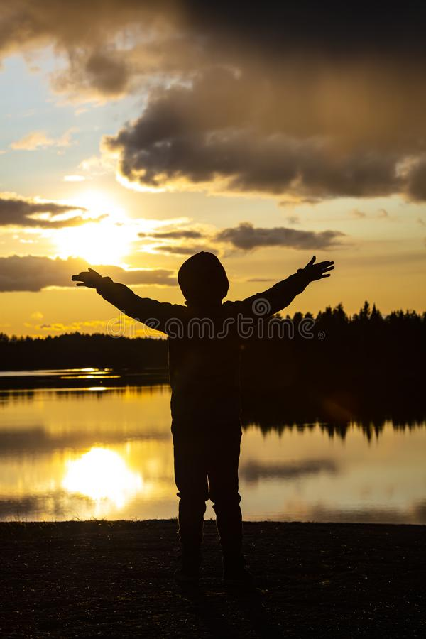 Мальчик и жёлтый закат в Финляндии Мальчик широко держит руки стоковая фотография rf