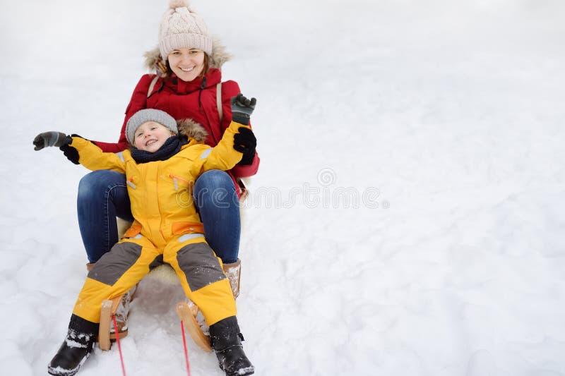 Мальчик и мать сползая в снег стоковые изображения