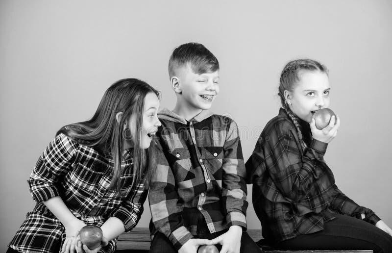 Мальчик и подруги едят закуску яблока пока ослабляющ Здоровое питание dieting и витамина Концепция закуски школы Группа стоковое фото