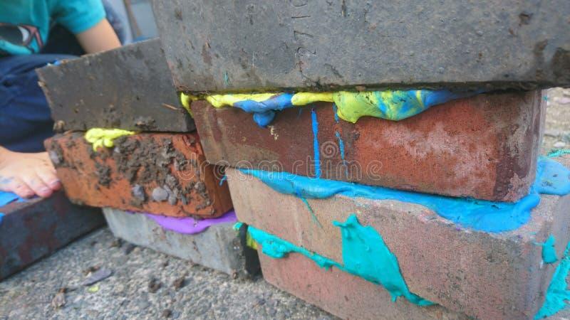 Мальчик кладя покрашенную замазку между кирпичами здания стоковые фото