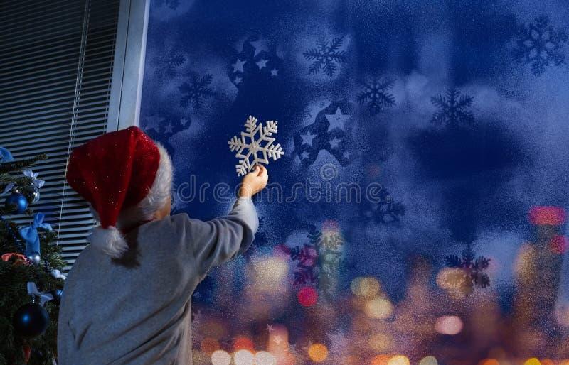 Мальчик кладя снежинку на окно стоковые изображения