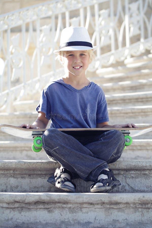Мальчик конькобежца сидя с longboard стоковое изображение rf