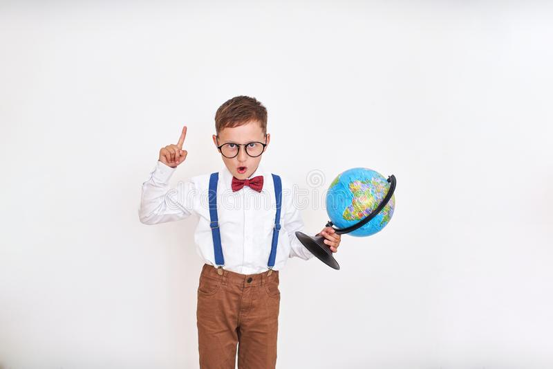 Мальчик кричит с его пальцем вверх, держащ глобус в его руках пришл вверх с идеей начало учебного года t стоковые изображения rf