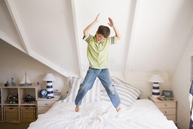 мальчик кровати его скача детеныши стоковые изображения