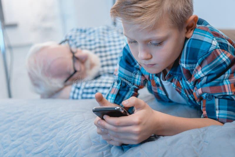 Мальчик лежа на кровати и используя его smartphone пока его granpa napping стоковые фотографии rf