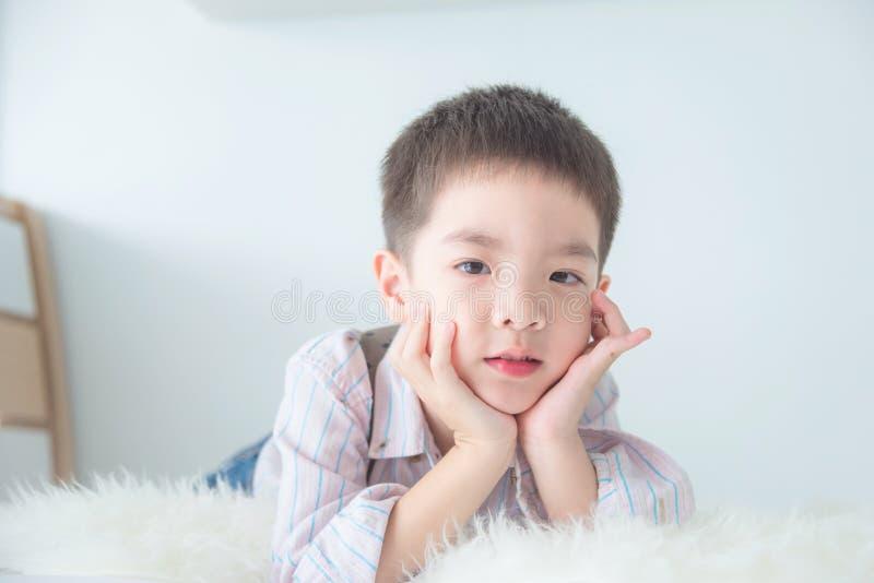 Мальчик лежа на кровати и смотря камеру стоковые фото