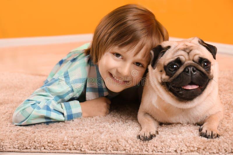 Мальчик лежа с милой собакой мопса на поле дома стоковые фото