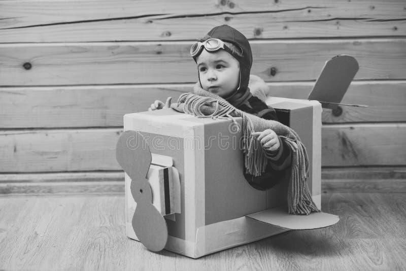 Мальчик маленького ребенка в пилотном костюме играет и мечтает стоковые фото