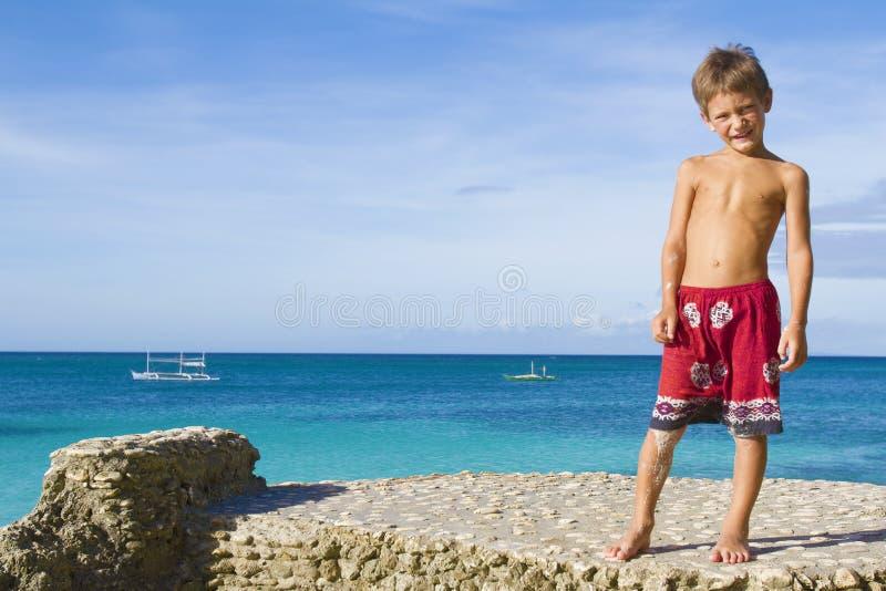 Мальчик маленького ребенка на утесах на тропическом backgroun моря стоковые фотографии rf